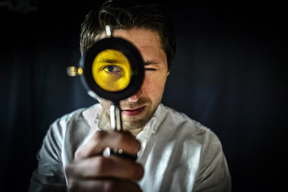 Researcher looking through a yellow lens. Photo.