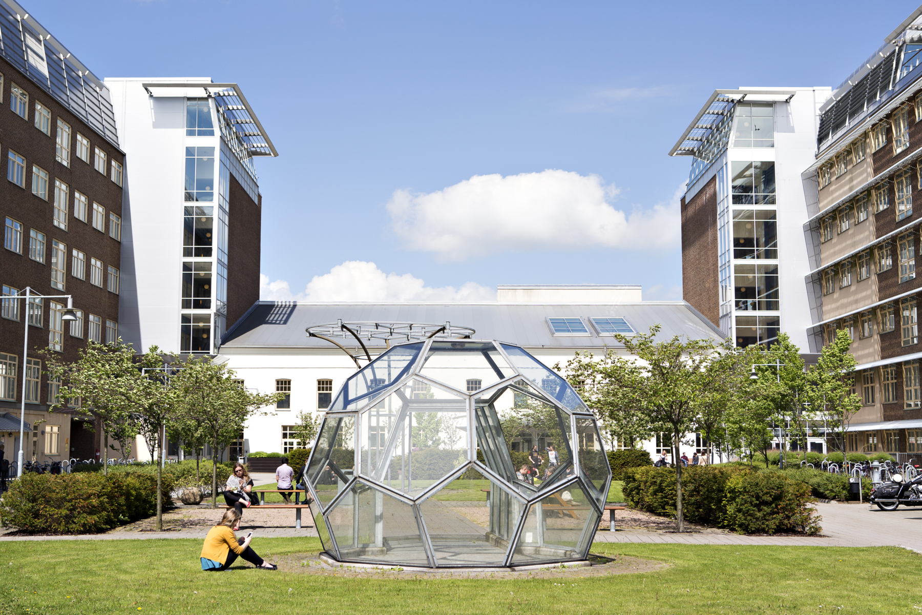 Photo of Campus Helsingborg on a sunny day. A person is sitting in the grass in front of a big glass building.